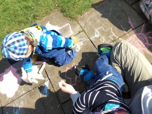 Mit Straßenmalkreide auf den Steinen vor unserer Laube malen...